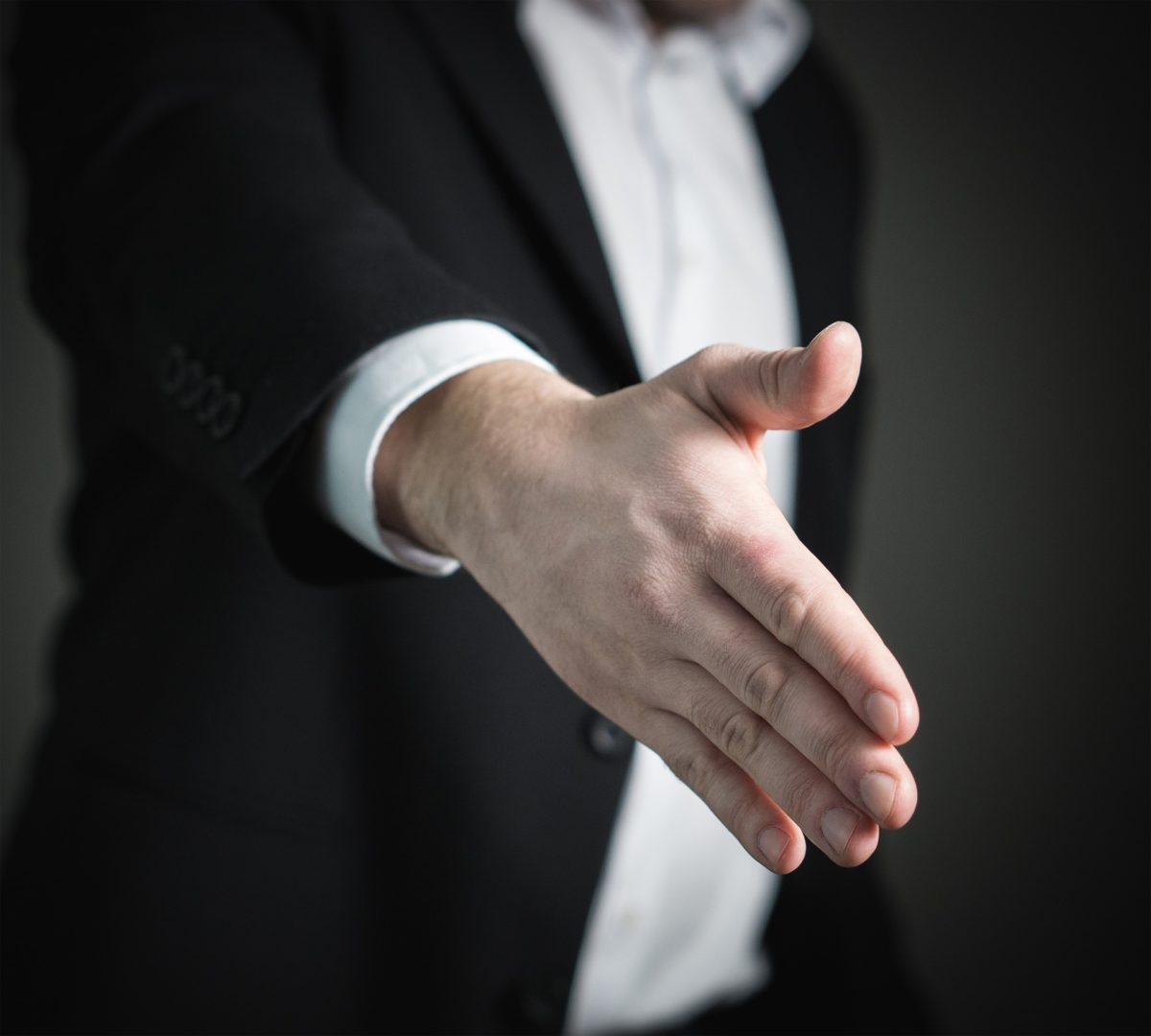 photo of a man extending his hand for a handshake